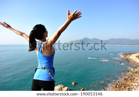 cheering woman hiker stand seaside rock looking the view with arms open  - stock photo
