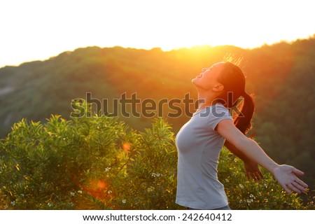 cheering woman open arms at sunrise mountain peak  - stock photo
