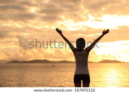 cheering woman open arms to sunrise at sea  - stock photo