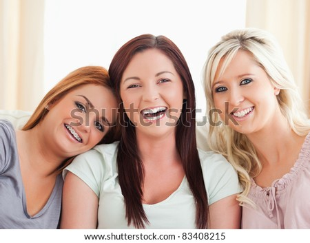 Cheering women sitting on a sofa in the living room - stock photo