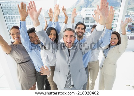 Cheering workers with raised arms in the office - stock photo