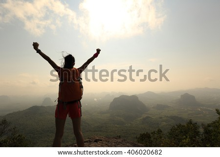 cheering young asian woman open arms on sunrise mountain peak rock