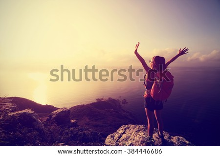 cheering young woman backpacker at sunrise seaside mountain peak - stock photo