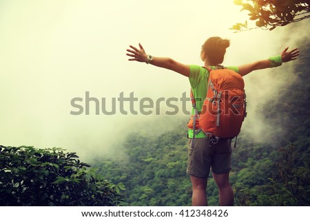 cheering young woman hiker open arms outdoor - stock photo