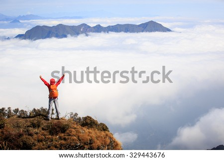cheering young woman hiker open arms to beautiful landscape on mountain peak - stock photo