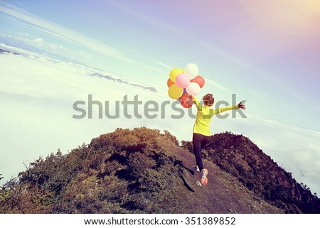 cheering young woman with colorful balloons on mountain peak - stock photo