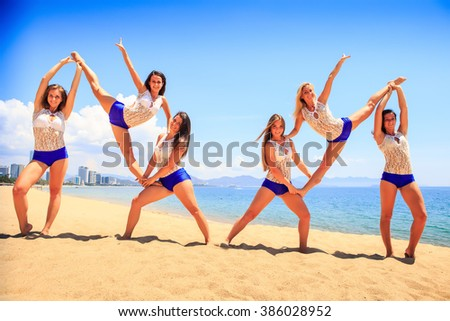 cheerleaders in white blue uniform perform double Heel Stretch on sand beach smiles against sea wind shakes long hair - stock photo