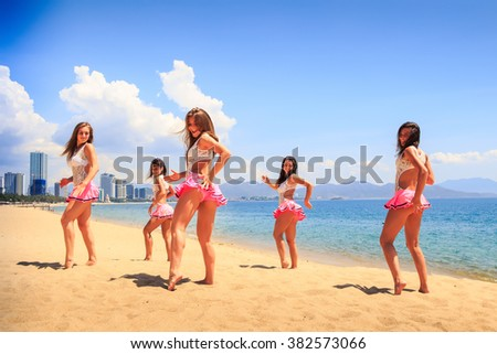 cheerleaders in white pink uniform dance with one hand aside on sand beach against resort wind shakes long hair