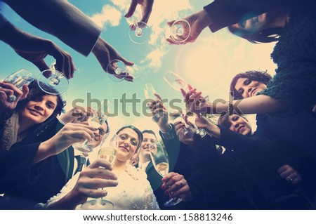 Cheers! A nice couple of newlyweds are toasting, they are surrounded by friends. The shot is from below. Vintage effect. - stock photo