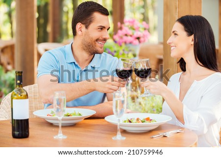 Cheers! Beautiful young loving couple toasting with red wine and smiling while relaxing in outdoors restaurant together