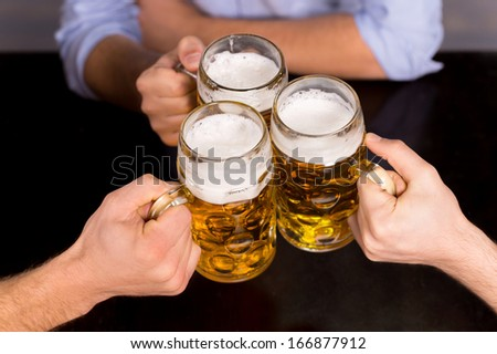 Cheers! Close-up top view of people holding mugs with beer - stock photo