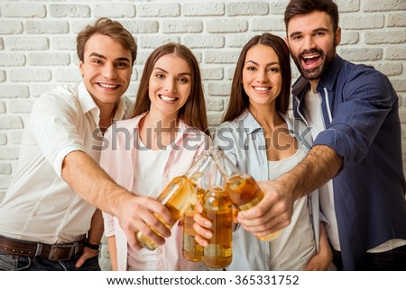 Cheers! Group of happy young people bonding to each other and stretching out bottles with beer standing on a background of brick wall