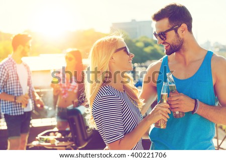 Cheers! Smiling young couple clinking glasses with beer and looking at each other while two people barbecuing in the background - stock photo