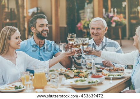 Cheers to family! Happy young and senior couples sitting at the dining table and toasting with wine - stock photo