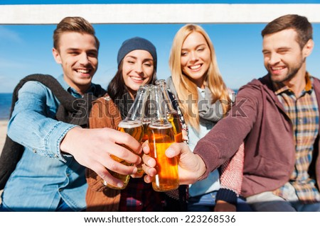 Cheers to friends! Group of young cheerful people cheering with beer and smiling while bonding to each other  - stock photo