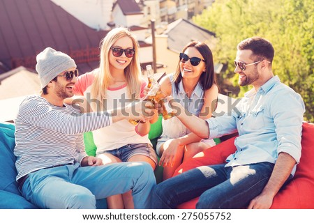 Cheers to friends! Top view of four young cheerful people cheering with beer and smiling while sitting at the bean bags on the roof of the building - stock photo