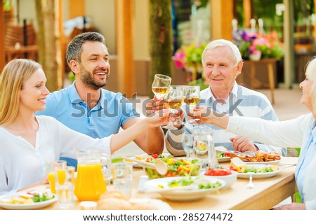 Cheers to the nearest! Happy young and senior couples sitting at the dining table and toasting with wine  - stock photo