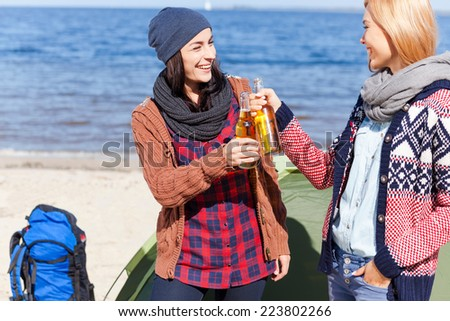 Cheers to us! Two beautiful young women cheering with beer and smiling while standing near their tent on the beach - stock photo