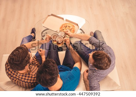 cheers!  top-view photo of happy men   celebrating victory and  clinking glass of beer - stock photo