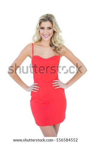 Cheery smiling blonde model posing with hands on hips on white background - stock photo