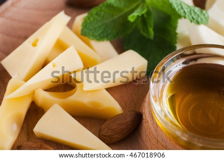 Cheese, almond and bowl with honey closeup. Natural organic snack, homemade products