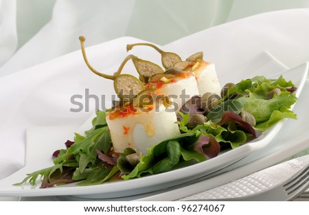 Cheese and capers sweet and sour sauce and pistachios in green leaves - stock photo