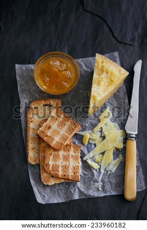 Cheese and crackers served on waxed paper and slate with jam - stock photo