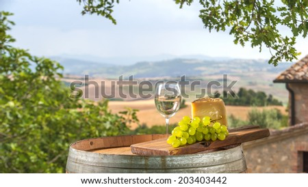 Cheese and grapes on a barrel in the Tuscan landscape Italy - stock photo