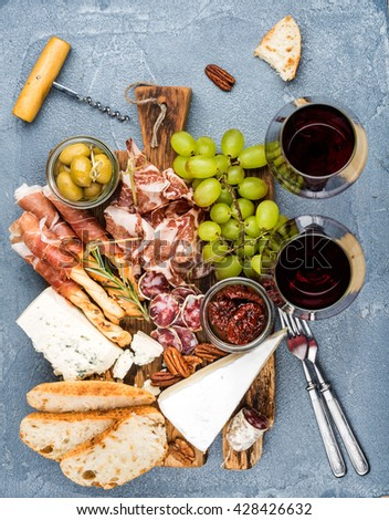 Cheese and meat appetizer selection. Prosciutto di Parma, salami, bread sticks, baguette slices, olives, sun-dried tomatoes, grapes and wooden board, glasses of red wine over grey backdrop, top view - stock photo