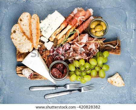 Cheese and meat appetizer selection. Prosciutto di Parma, salami, bread sticks, slices, olives, sun-dried tomatoes, grapes and nuts on rustic wooden board over grey concrete backdrop, top view - stock photo