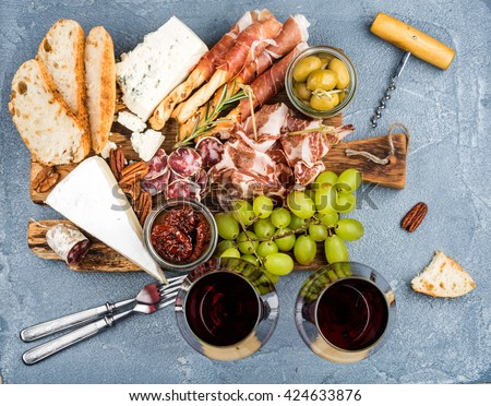 Cheese and meat snack selection. Prosciutto, salami, bread sticks, baguette slices, olives, sun-dried tomatoes, grapes and nuts on rustic wooden board, two glasses of red wine, top view - stock photo