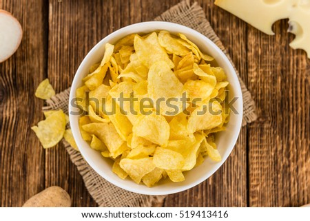 Cheese and Onion Potato Chips on a vintage background as detailed close-up shot (selective focus)