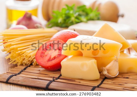 Cheese and pasta with ingredients on wood background - stock photo