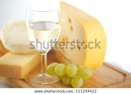 cheese and wine on a wooden table - stock photo