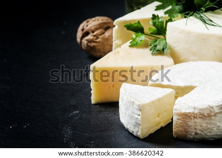 Cheese Assortment on a dark background, selective focus - stock photo