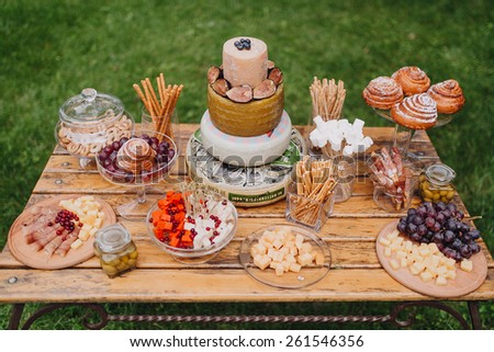 cheese bar on a wooden table on a background of green grass - stock photo