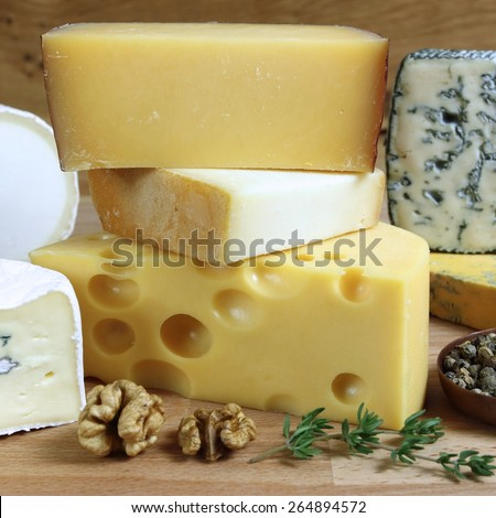 Cheese board - various types of soft and hard cheese. International dairy delicacies. - stock photo