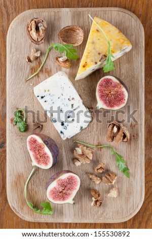 Cheese board with blue cheese, nut cheese, fresh figs and nuts - stock photo