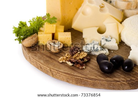 cheese board with cheeses, walnuts and black olives