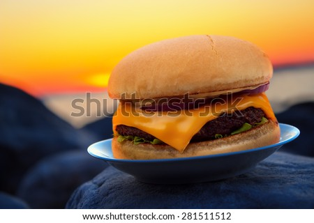 Cheese burger on beach rock in evening sunset - stock photo
