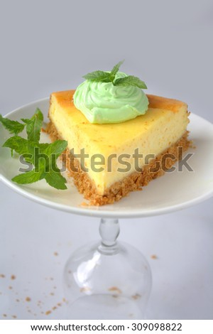 Cheese cake with mint cream on top and mint leaves background