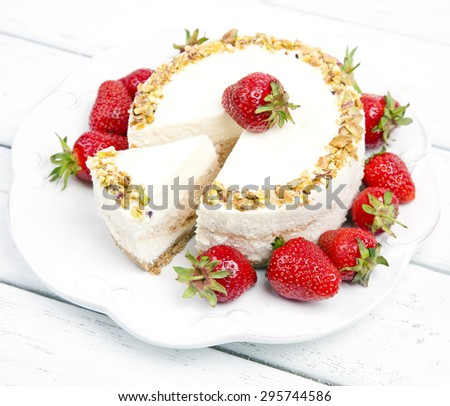 cheese cake with strawberries on a wooden white table