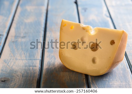 Cheese chunk on painted wooden board - stock photo