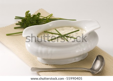 Cheese dip in a white sauce-boat. Salad dressing.