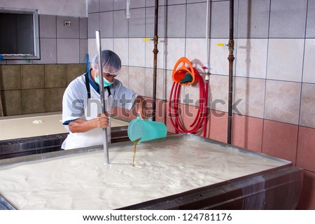 Cheese factory worker processing fermenting milk