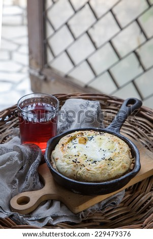 Cheese-filled bread with egg and glass of  red wine. Khachapuri - stock photo