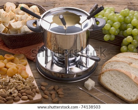 Cheese fondue rechaud, apricots, Walnuts, Almonds, Grapes and Bread. - stock photo