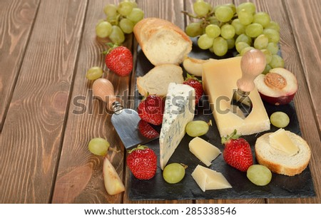 Cheese, grapes and fruit on a brown background - stock photo