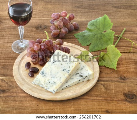Cheese, grapes and leaves,  and a glass of wine on wooden surface