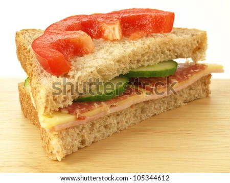 Cheese, ham and salami sandwich with slice of pepper - stock photo